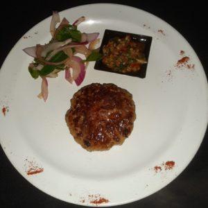Hamburguesa de cordero con salsa criolla y vegetales marinados
